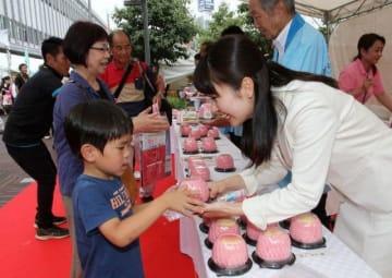 桃の新品種「さきがけはくとう」をプレゼントされる来場者(左)