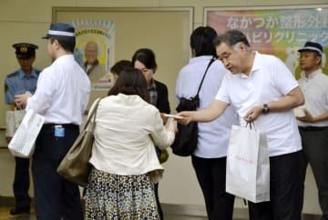 吉川友梨さんが行方不明になった事件で、情報提供を求めるポケットティッシュを配る父永明さん(手前右)と捜査員=2日朝、大阪府熊取町