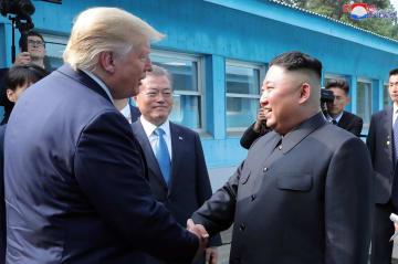 6月30日、板門店で対面したトランプ米大統領(左)と北朝鮮の金正恩朝鮮労働党委員長。中央奥は韓国の文在寅大統領(朝鮮中央通信=共同)