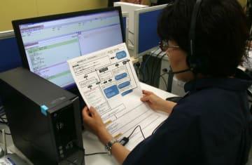マニュアルを見ながら電話をかけるオペレーター=長崎市内