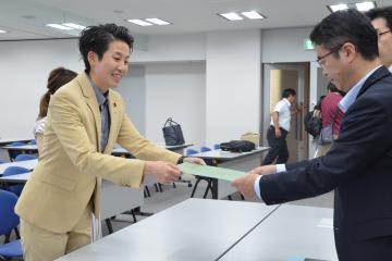 県の担当者に宣誓書類を提出する滑川友理さん(左)=県庁