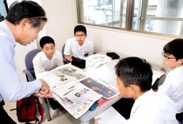 藤本支社長(左)から新聞記事について解説を受ける生徒