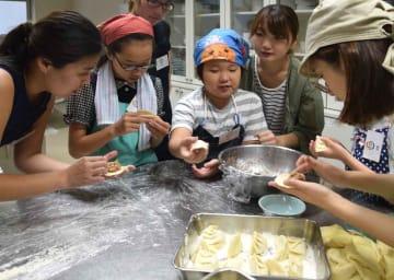 学生に教わりながらギョーザを作る子どもたち(滋賀県草津市野路・市民交流プラザ)