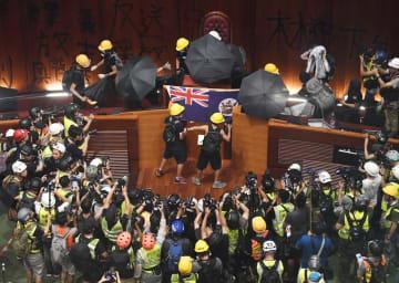 立法会の議場に、英植民地時代の旗を掲げるデモ隊。周囲をメディアが取り囲んだ=1日、香港(共同)