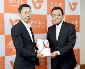 寄贈物の目録を手にした松岡隼人市長(左)と上竹清続代表理事=人吉市