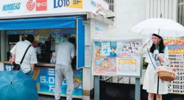 サマージャンボ宝くじを買い求める人たちと購入を呼び掛ける中島晴香さん(右)=2日午前、大分市