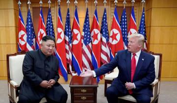 6月30日、板門店の韓国側施設で会談するトランプ米大統領(右)と北朝鮮の金正恩朝鮮労働党委員長(ロイター=共同)