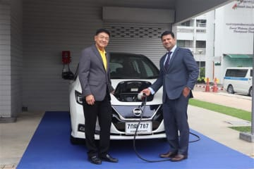 Sompong Preeprem (L), governor of the Thai Provincial Electricity Authority (PEA), and Remesh Narasimhan, president of Nissan Motor (Thailand) Co., demonstrate how to charge batteries at a charging station in Bangkok on June 18, 2019.