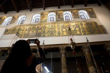 聖誕教会内部の修復されたフレスコ画を撮影する観光客=2018年12月、ヨルダン川西岸のパレスチナ自治区ベツレヘム(AP=共同)