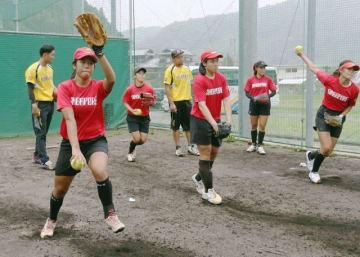 平林金属クの選手(黄色のユニホーム)から助言を受けながら投球練習するシンガポール女子代表メンバー=HIRAKINライズ球場