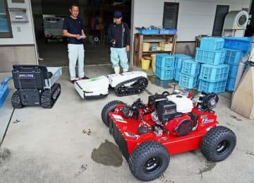 リモコンで操作する草刈り機(右2台)と運搬車(左)=和歌山県みなべ町東本庄で