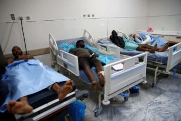 移民収容施設への空爆を受け、病院で手当てを受ける負傷者=3日、リビア・トリポリ(ロイター=共同)