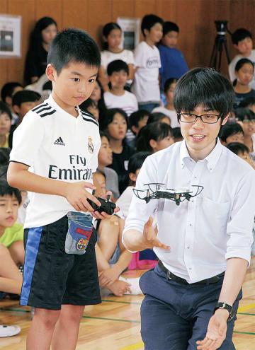 真剣な表情でドローンを操作する児童