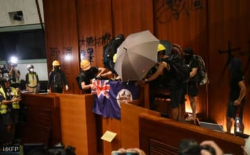 Protesters unfurl the flag of colonial Hong Kong at the podium in the occupied legislature. Photo: Thammakhun John Crowcroft/HKFP.