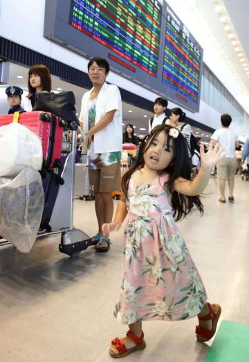 昨年8月、夏休みの海外旅行から帰国し、笑顔で手を振る女の子=成田空港