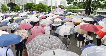 参院選が公示され、雨の中での街頭演説に聴き入る有権者ら=4日午前11時10分、JR桜木町駅前