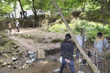 渓流の脇にカメラなどを設置する広島市立大の学生ら=6月、広島市安佐北区