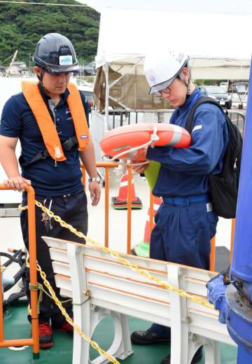 荒神丸の救命設備の点検をする運航労務監理官(右)=唐津市湊港