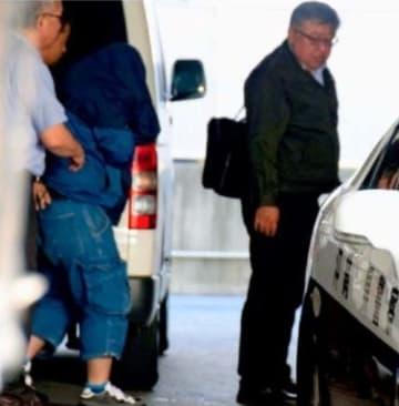 強盗殺人容疑に先立ち、窃盗容疑で逮捕され嘉手納署に連行される容疑者(左から2人目)=5月23日午後5時40分ごろ