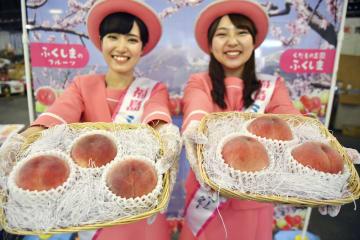 出荷が本格化した福島県特産のモモをPRする女性=5日午前、福島市