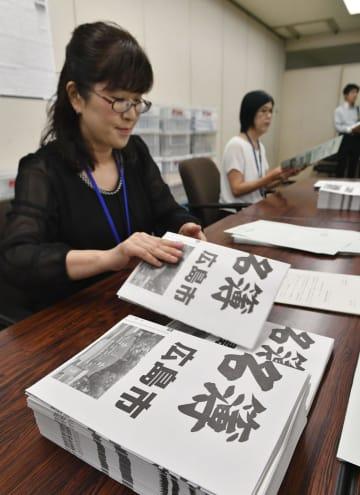 広島市役所で発送作業が行われる、引き取り手のない原爆死没者の名前が書かれたポスター=5日午前