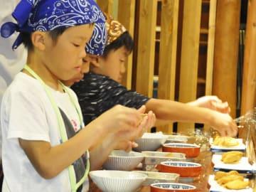 真剣な表情で、いなりずしを握る子どもら=関市本町、丸吉寿司