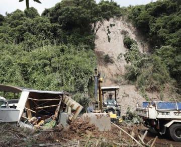 重機を使って土砂を撤去する作業員=5日午前9時36分、鹿児島市光山