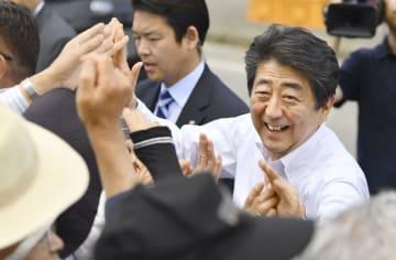 街頭で有権者とタッチを交わす自民党総裁の安倍首相=5日午前、新潟県村上市