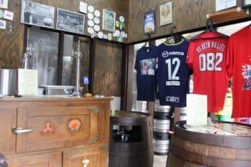 テーブル代わりの樽が並ぶ店内は昭和レトロな雰囲気。壁には地元愛溢れる広島カープとサンフレッチェ広島のグッズが飾られている