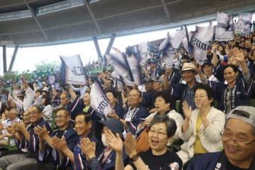 旗を振ったり、拍手をしたりして盛り上がる市民応援ツアー参加者(日南市観光協会提供)