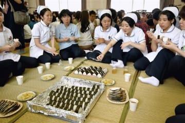 天草大水害の際、住民に配られた炊き出しと同じメニューを食べて当時をしのぶ上天草看護専門学校の学生ら=上天草市