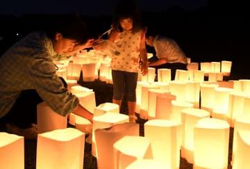 九州北部の豪雨から2年となり、福岡県朝倉市の東林田集落で祖母と紙灯籠をともす女の子=5日夕