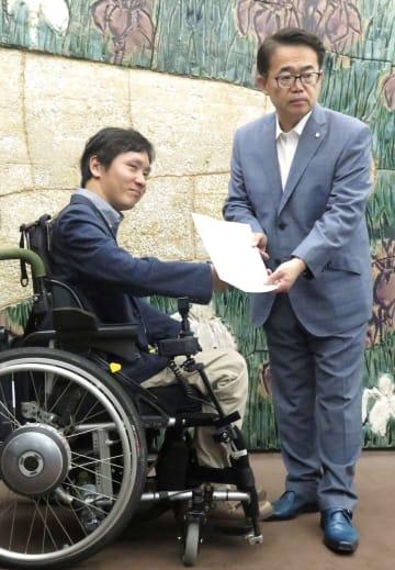 愛知県の大村秀章知事(右)に申立書を提出する障害者団体のメンバー=5日午後、名古屋市