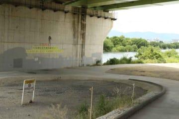 宇治川沿いでバーベキューの人気スポットとなっている高架下。橋脚や周囲にはごみの持ち帰りを訴える掲示がある(宇治市莵道)