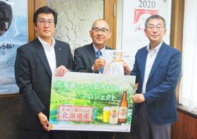 岡村副町長(中央)に善意を贈った金丸本部長(左)と柴田専務理事
