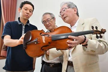 修理が完了した紺野陽吉の愛用バイオリンを手に取る、白鷹町文化交流センターあゆーむの橋本淳一館長(右)ら=同所