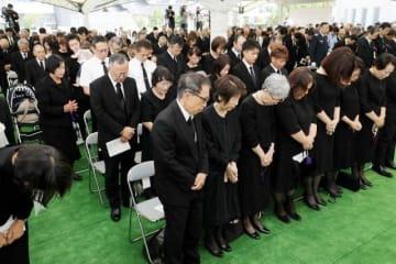 西日本豪雨から1年を迎え、岡山県倉敷市の追悼式で黙とうする真備町地区の遺族ら=6日午前10時4分、同地区