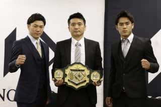山口プロデューサー(中央)の持つベルトを挟む江幡(左)と小笠原(右)