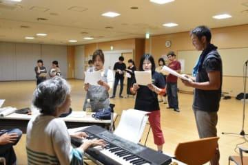 初稽古で劇中歌の練習に励む劇団「たそかれ」の団員たち