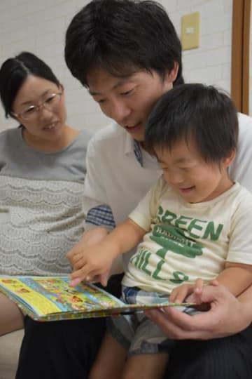 家族でくつろぐ岡崎組の岩本さん(中央)。第1子が生まれ「妻の手助けになれば」と2016年に育休を取得した=宮崎市