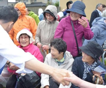 街頭演説後に候補者と握手する有権者たち=ひたちなか市内