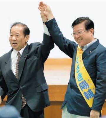 礒崎陽輔候補の手を取り、支援を呼び掛ける二階俊博幹事長(左)=7日夜、大分市の大南公民館