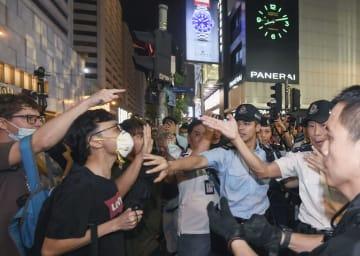 香港・九竜地区の繁華街で小競り合いになるデモ隊(左)と警察官ら=7日(共同)