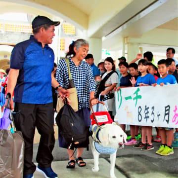 金城美千代さん(手前左から2人目)を先導しながら、船へ向かう盲導犬リーチ=伊江港