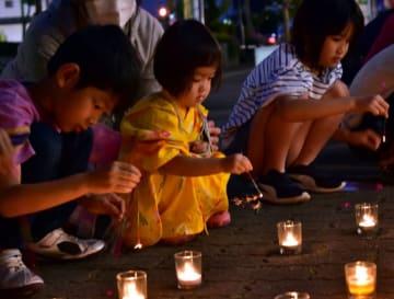 奥州市まちなか交流館前で線香花火をする子どもたち