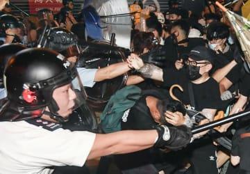 香港・九竜地区で警官隊(左)に強制排除されるデモ隊=7日(共同)
