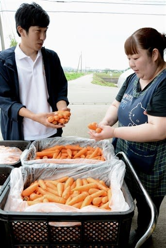 「まゆみ農園」の眞弓恵理子さんから、「フリフル」に出品するニンジンを受け取る坂口龍也さん(左)=6月、菊陽町