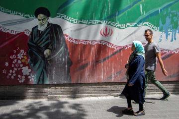 7日、イラン・テヘランで、故ホメイニ師の壁画の前を歩く人々(WEST ASIA NEWS AGENCY提供、ロイター=共同)