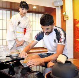 茶せんで茶をたてるビジャ(右)=神戸市中央区下山手通1、生田神社