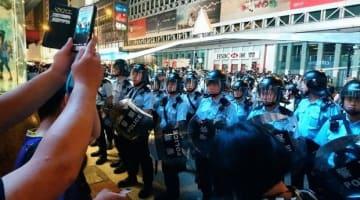 繁華街の旺角の大通りで一部の抗議者と警察が対峙した。周辺は物々しい雰囲気に包まれた=7日夜(NNA撮影)